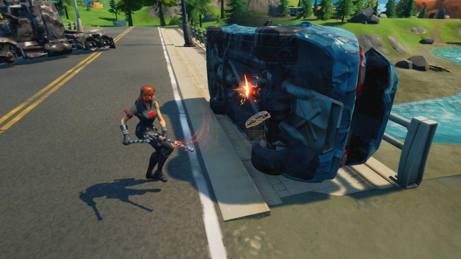 Le joueur pirate une voiture retournée pour récolter des pièces mécaniques à fabriquer dans Fortnite. Un camion qui a explosé est proche.