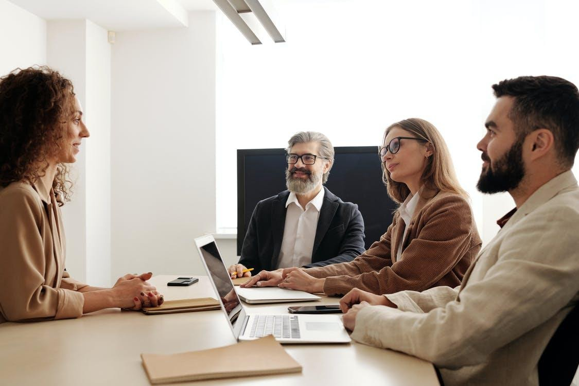 Homme et femme assis sur une chaise devant Macbook Pro