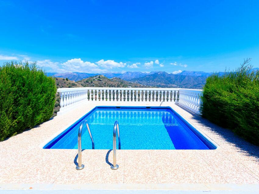 une piscine entourée de verdure devant des montagnes